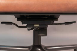Mechanism under the seat with two levers to adjust the seat height